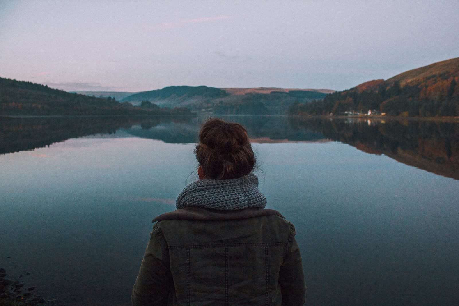 Back of woman in jacket and scarf looking at lake and hills.