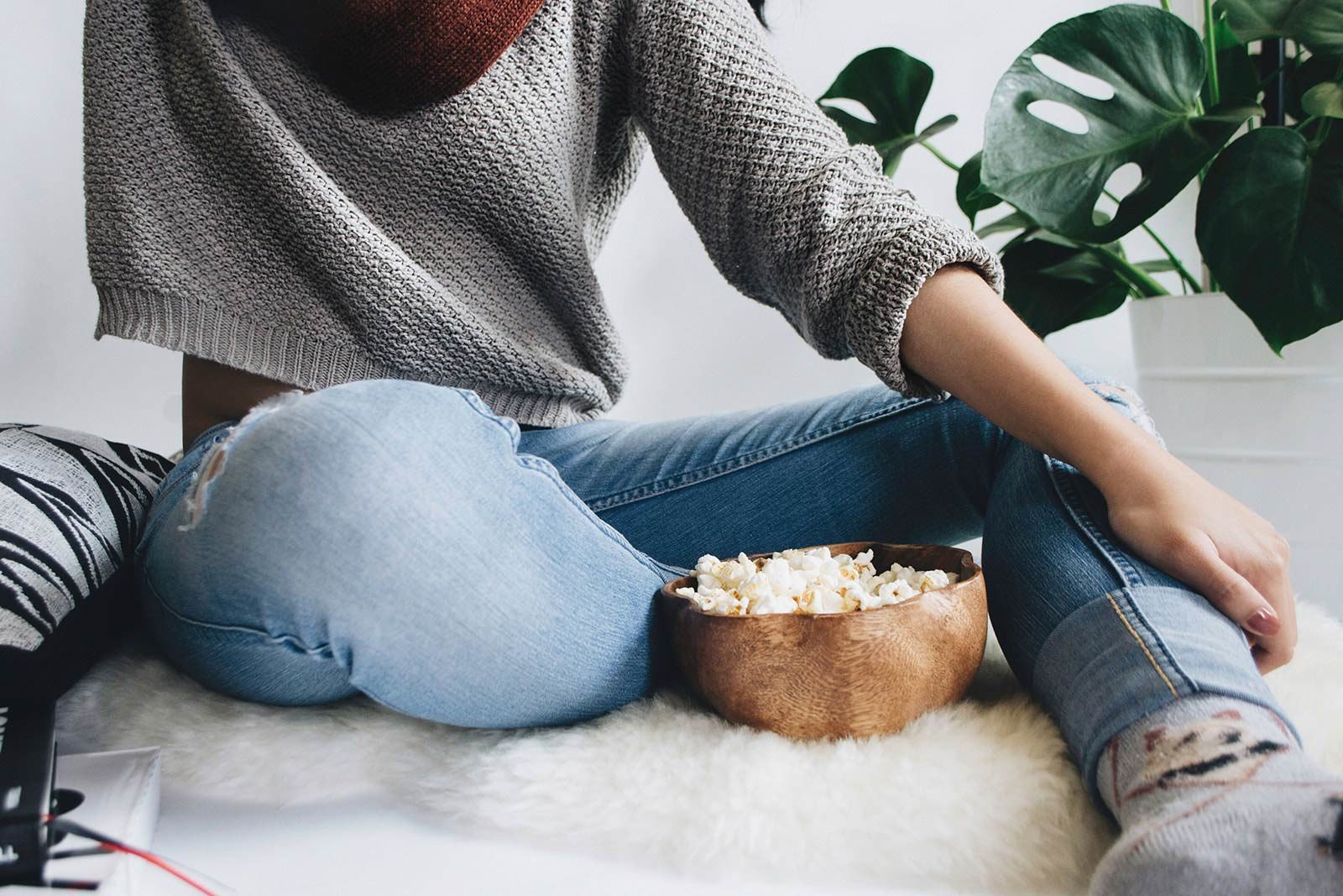 Woman in sweater and jeans sitting on carpet next to plant with bowl of popcorn.