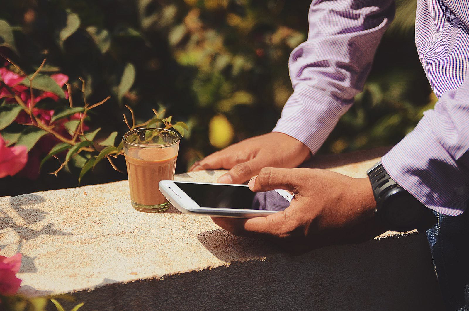 Man's arms leaning on cement block on cellphone next to flower bush and brown drink.