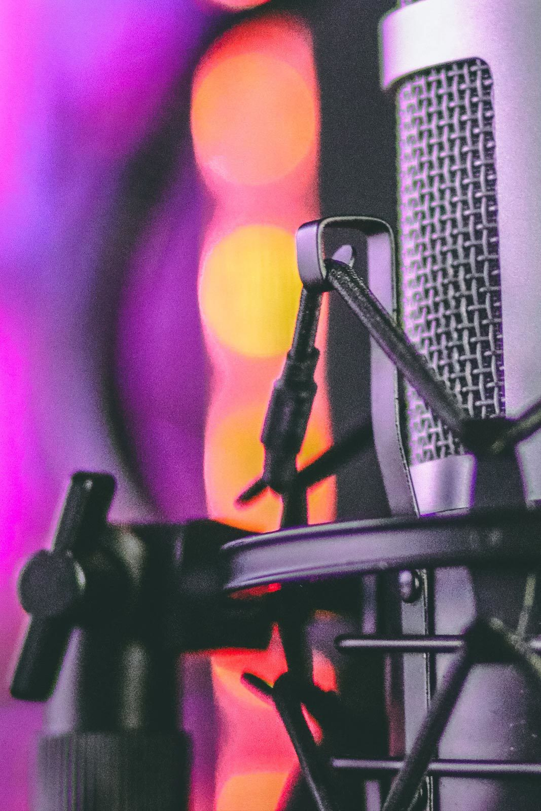 Closeup of microphone in front of purple lights.