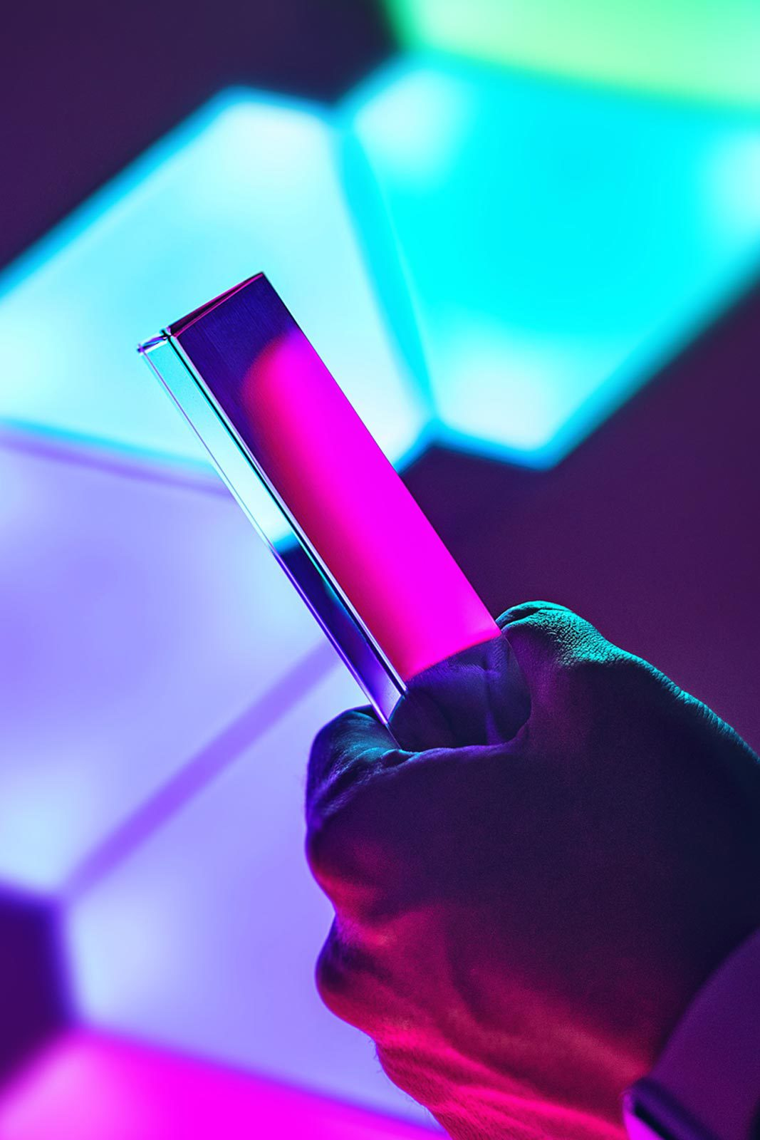Hand holding smartphone in front of blue, purple, and pink geometric lights.