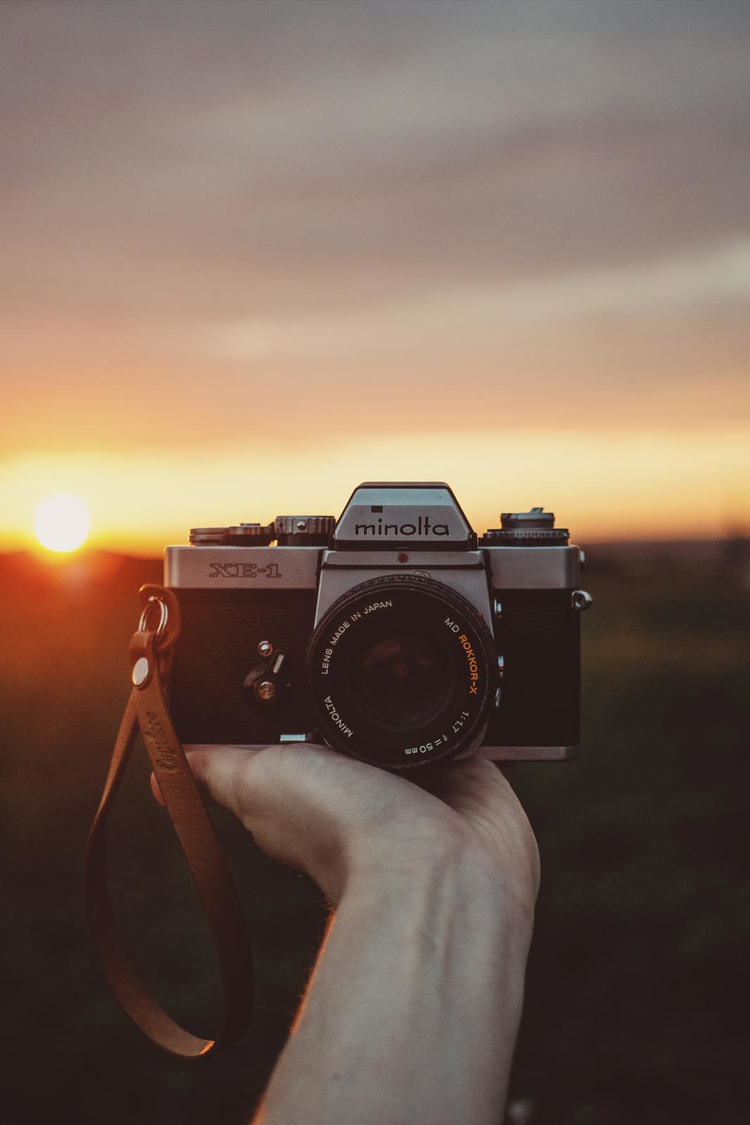 Hand holding camera over field with sunset.