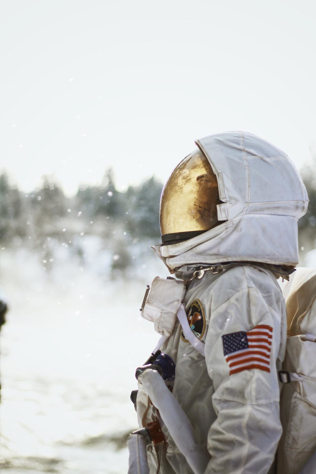 Astronaut with American flag on sleeve looking up in snowy field.