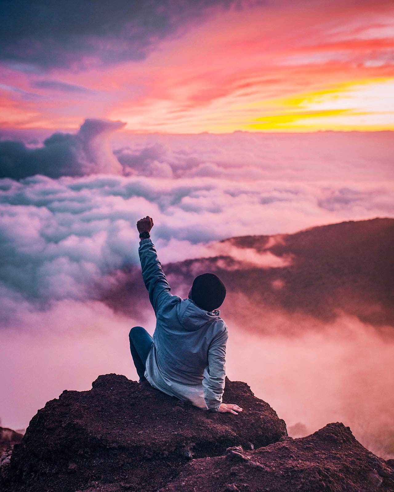 Person sitting on rock with fist in air over clouds.