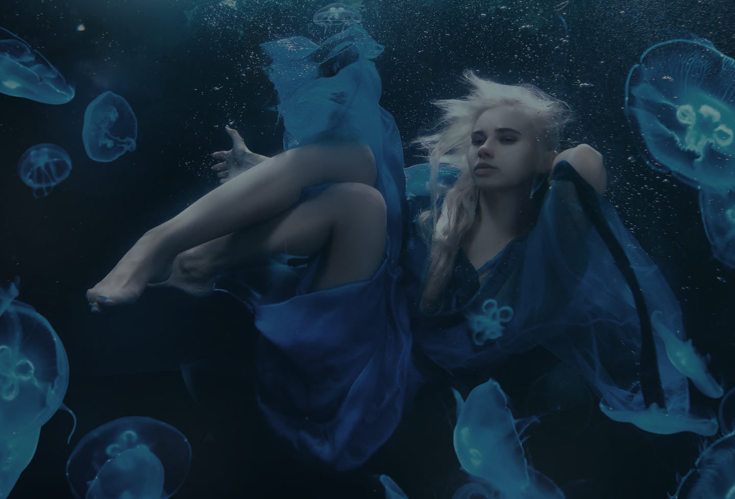 Woman in long flowing dress posing underwater with blue jellyfish.