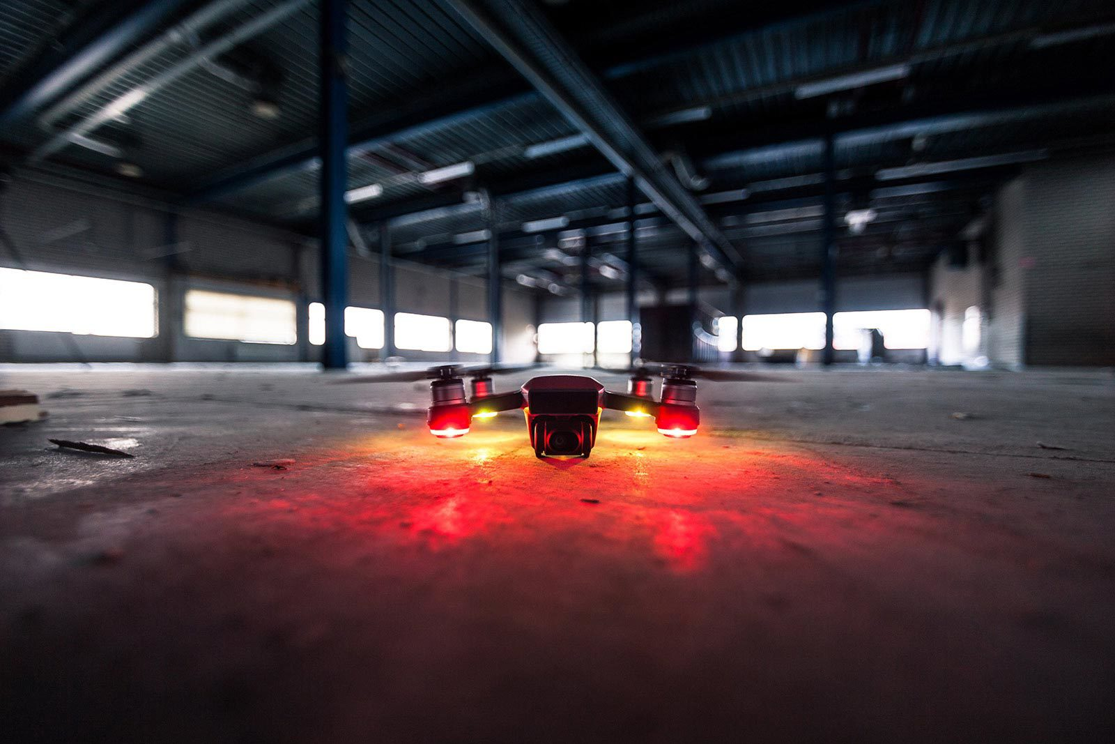 Red lighted drone sitting on cement ground in empty warehouse.