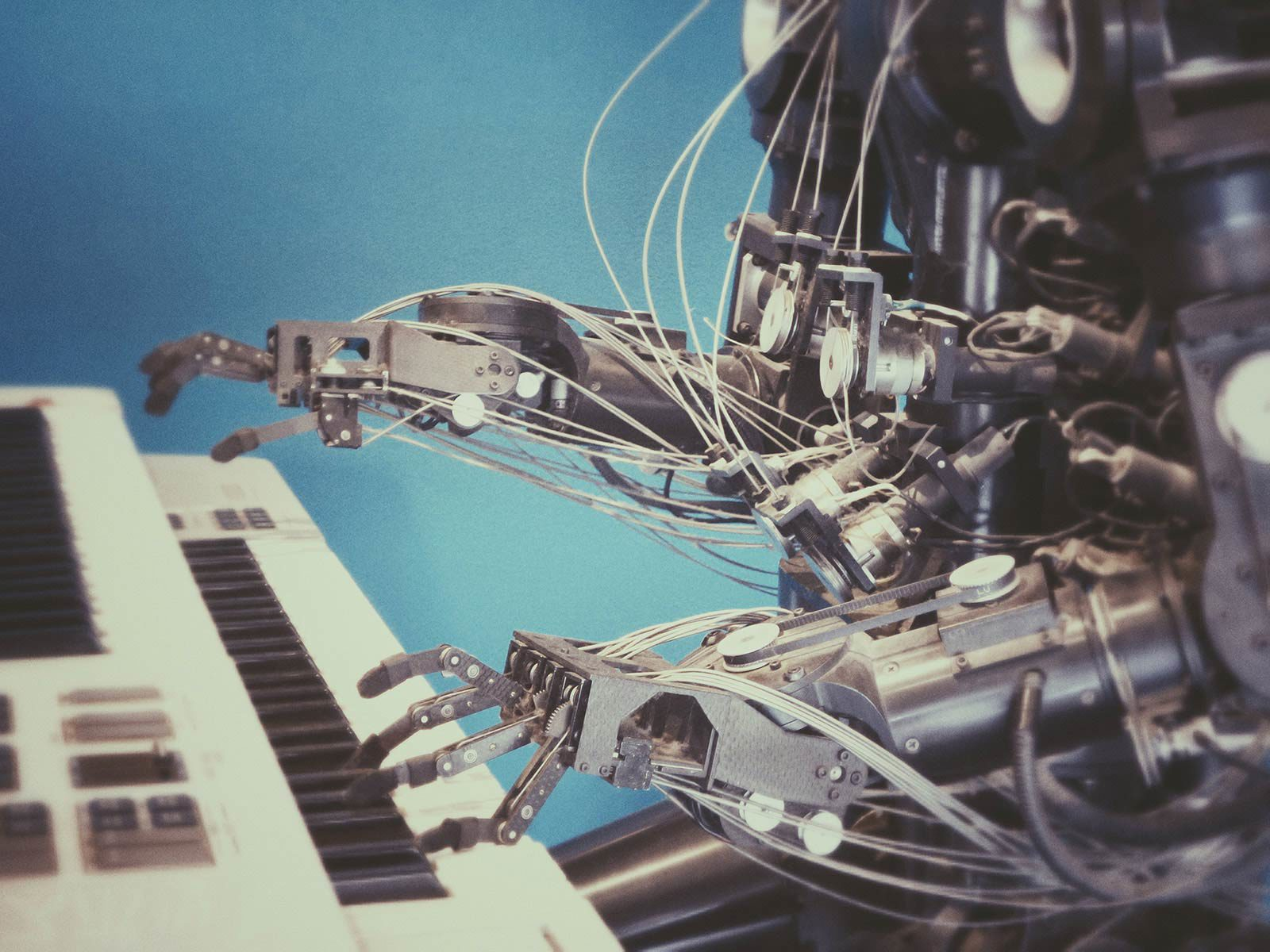 Robot playing keyboard against blue background.