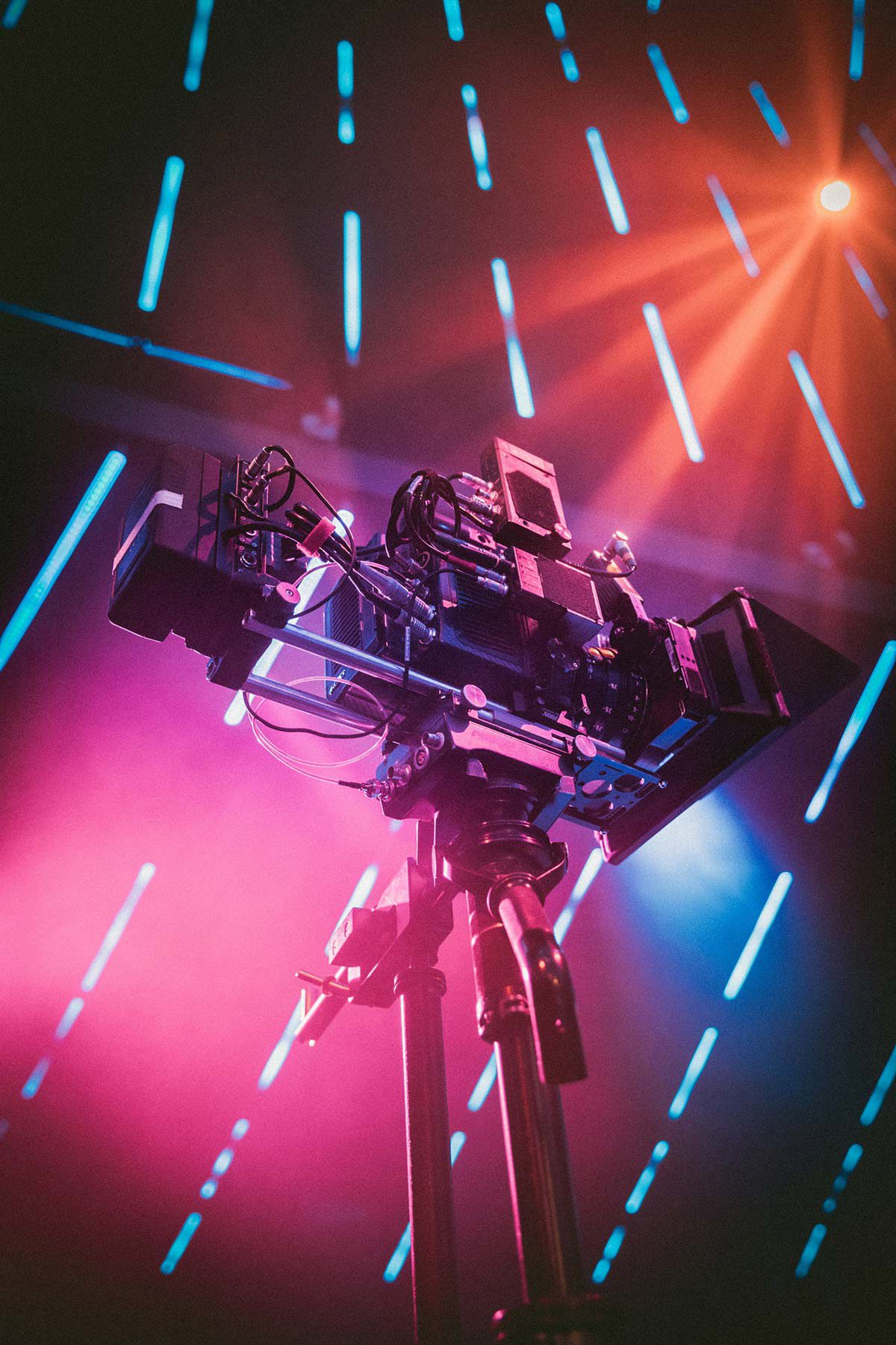 Large television camera next to bright orange and purple lights.