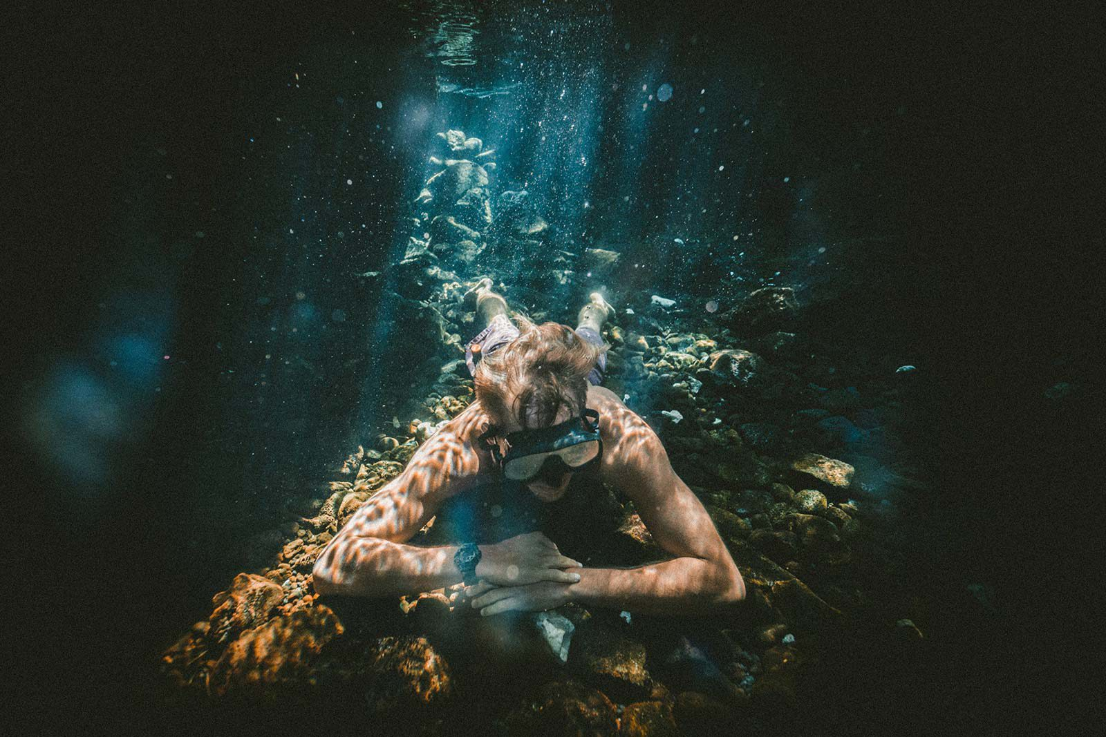 Person in goggles lying on coral underwater.