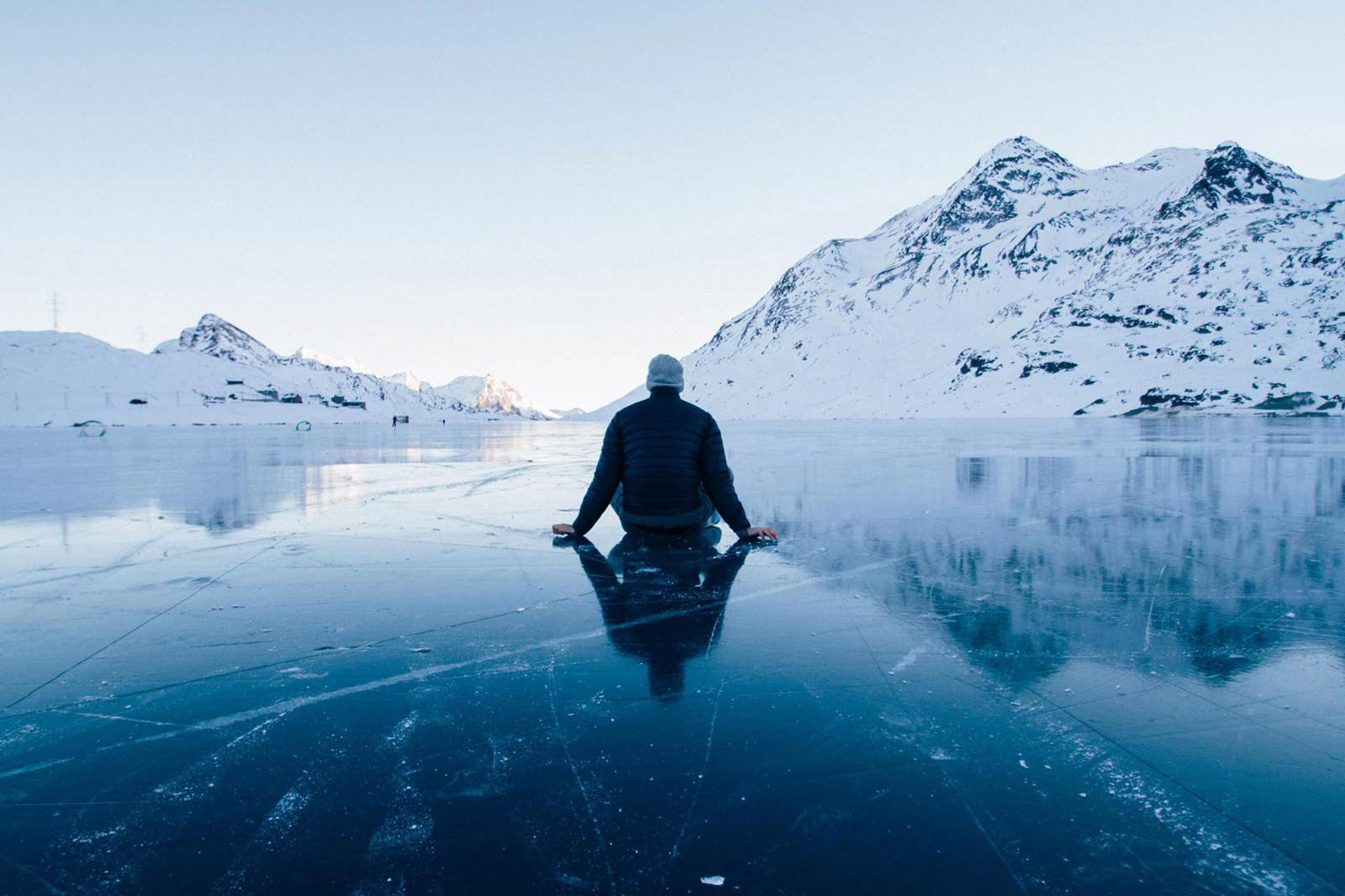 Man with back turned sitting on ice surrounded by snowy mountains.