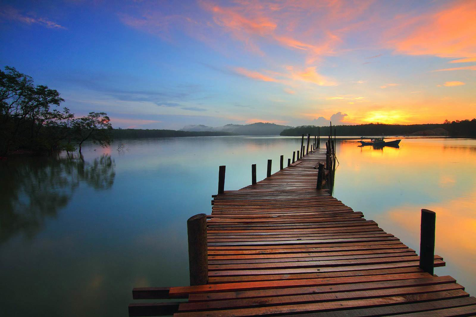 Long wooden pier and small boat on still water reflecting blue and orange sky.