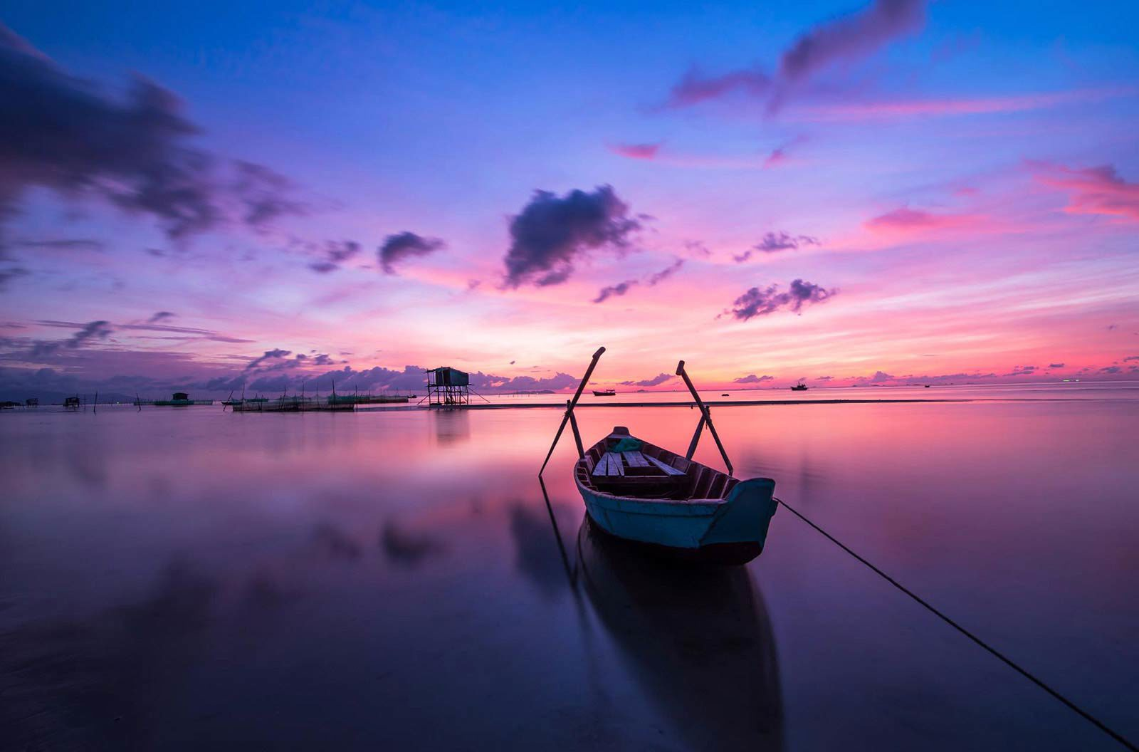 Row boat in middle of still water reflecting blue, pink and purple sky.