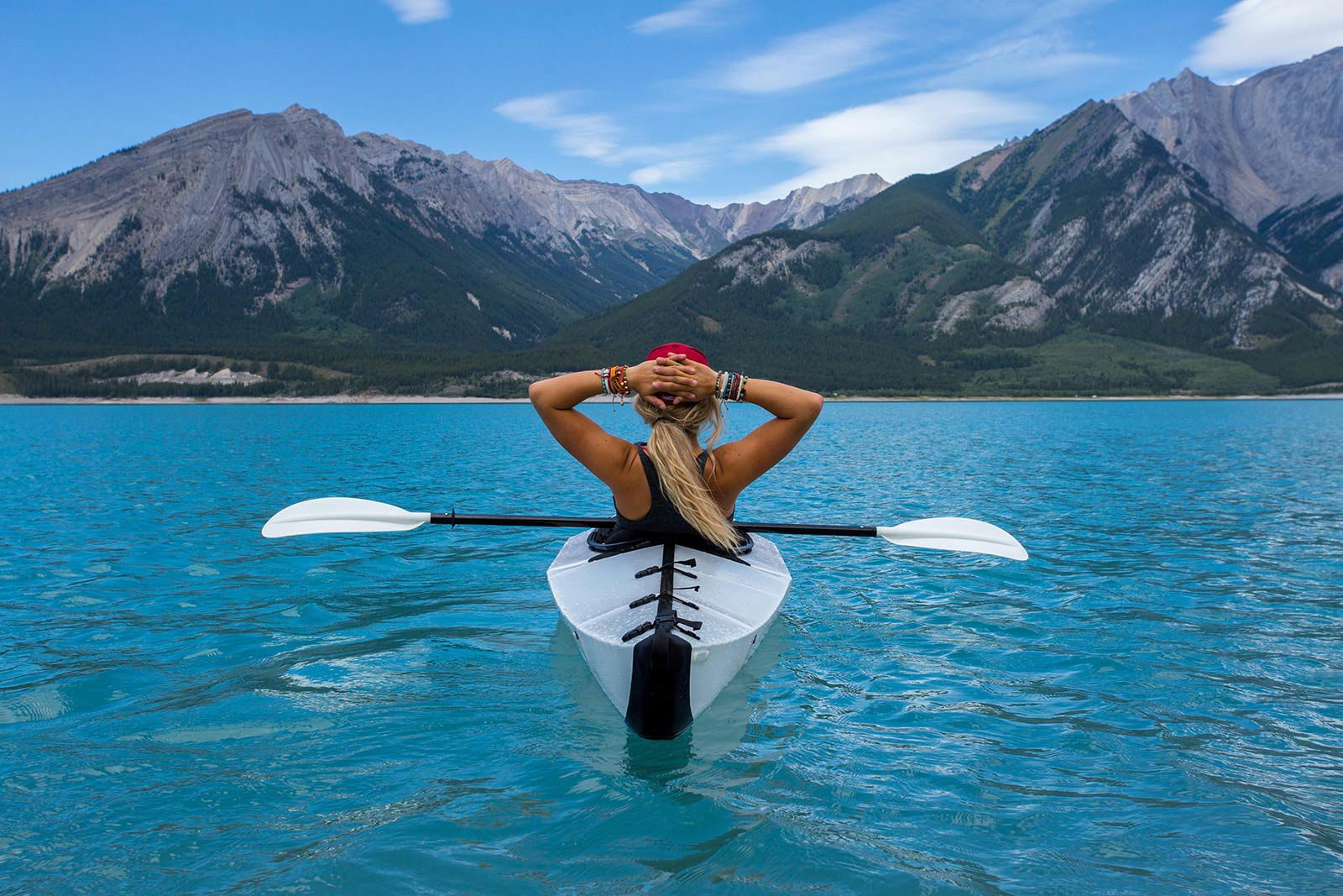 Woman with ponytails with hands on back of head in kayak looking at mountains.