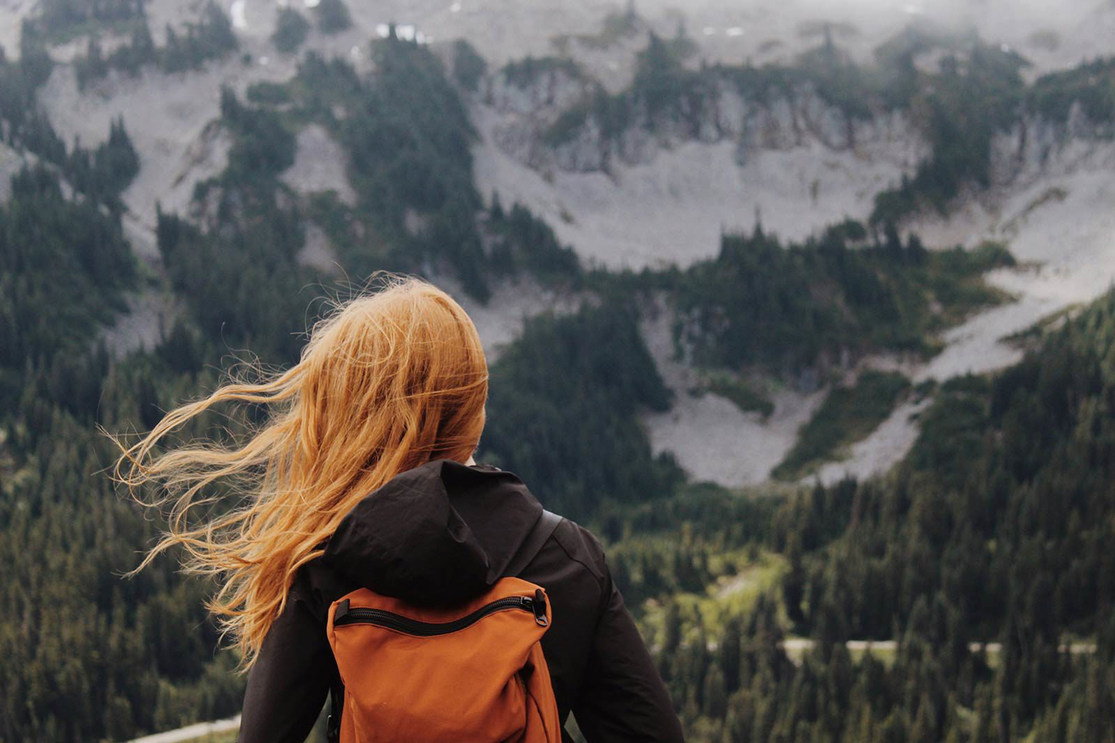 Back of woman with backpack and hair blowing looking and mountains.