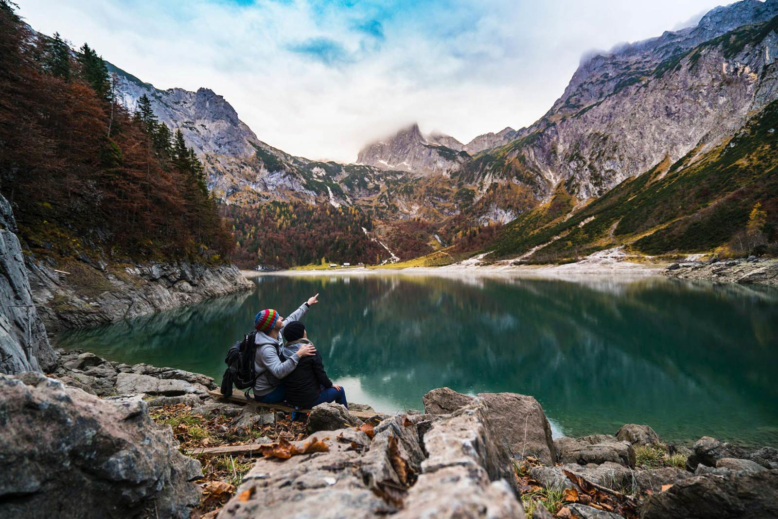 Man sitting with woman next to lake pointing at mountains.