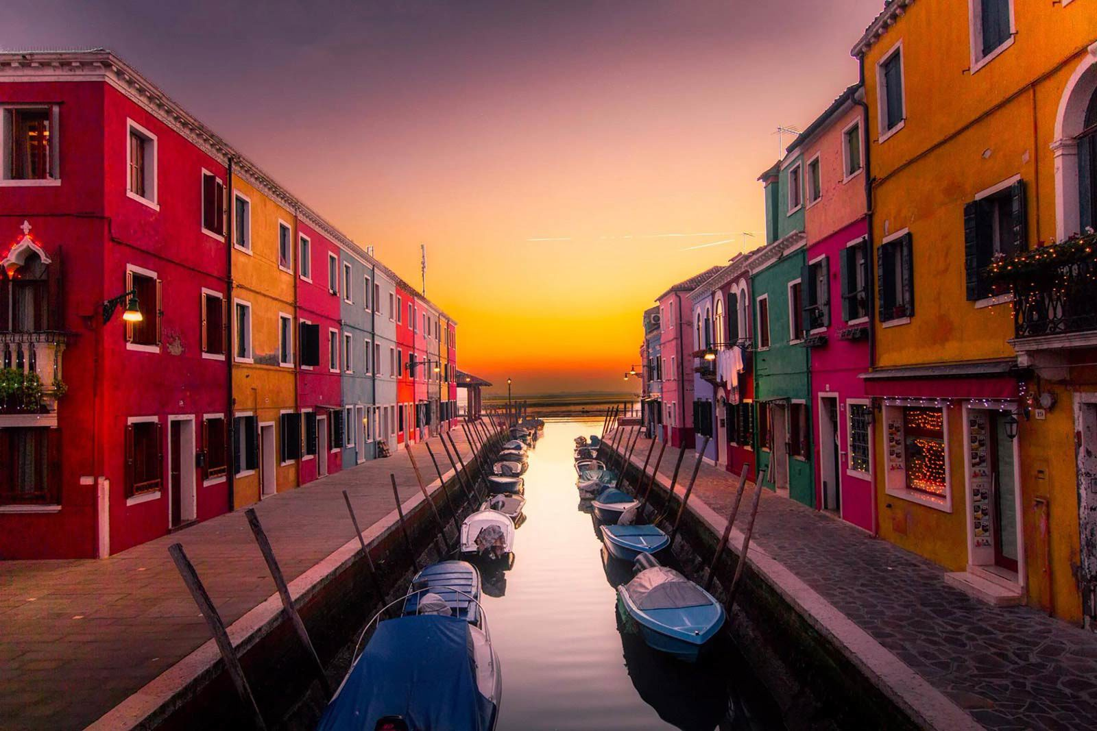 Rows of coloured houses next to canals with boats and sunset in distance.