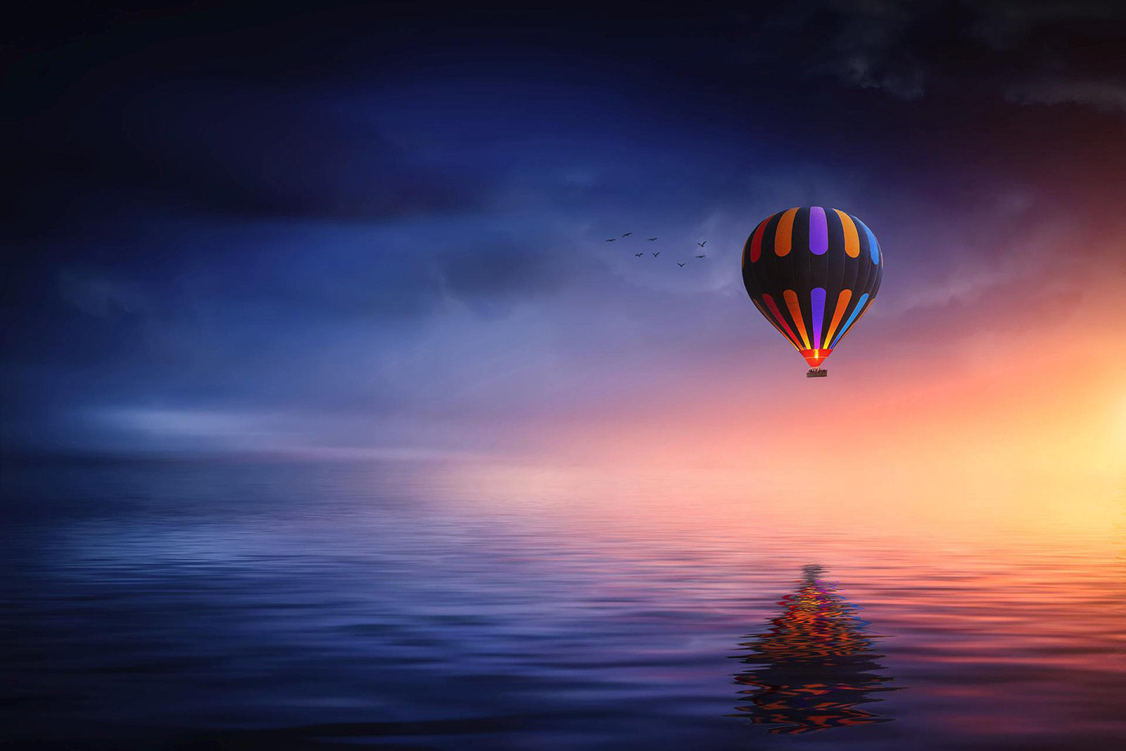 Hot air balloon and birds fly through sunset, reflecting in water below.