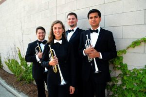 Four men and woman in bowties holding trumpets.