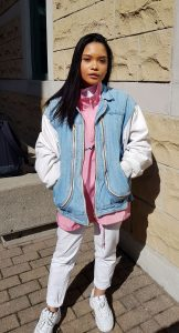 Portrait of woman in pink top, denim vest and white pants standing outside.