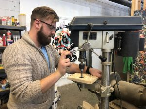 Man using drill press in workshop to drill hole in charcuterie board.
