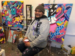 Man sitting with cup in front of colourful contemporary paintings.