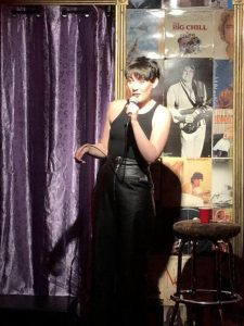 Woman talking into microphone on stage with purple curtain and posters