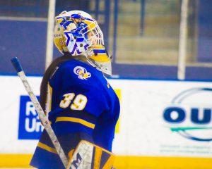 Side profile of goalie wearing Ryerson hockey jersey on ice.