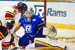 Goalie wearing Ryerson hockey jersey defending net against opponent.