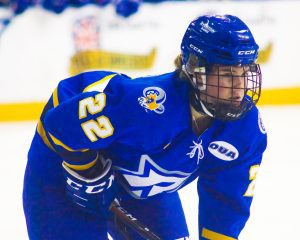 Ryerson hockey player on ice in defensive position.