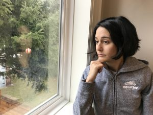 Woman sitting next to window with head resting on hand.