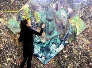 Woman with brush working on large abstract painting on wall.