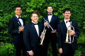 Four men standing in front of shrub in bowties holding trumpets.