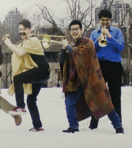Three men in snow dancing with trumpets.