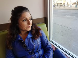 Woman in blue jacket sitting on booth looking out window.