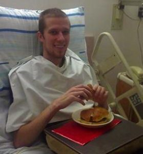 Man in hospital bed eating.