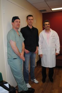 Man standing with doctor and nurse.