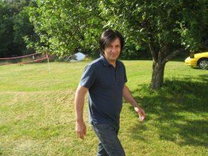 Man walking on field of grass near tree looking at camera.