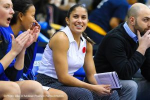 Woman sitting bench side at basketball game wearing poppy and smiling.
