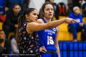 Woman speaking and pointing to woman wearing Ryerson Rams jersey