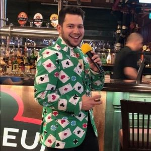 Man in bar wearing casino card blazer smiling holding microphone.