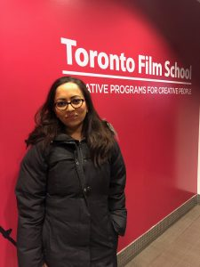 """Woman in winter jacket standing in front of red wall reading """"Toronto Film School""""."""