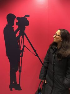 Woman looking at silhouette of man with camera on wall.
