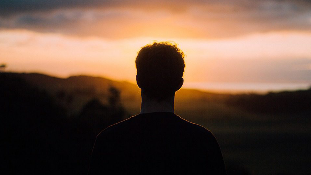 Silhouette of man looking towards sunset.