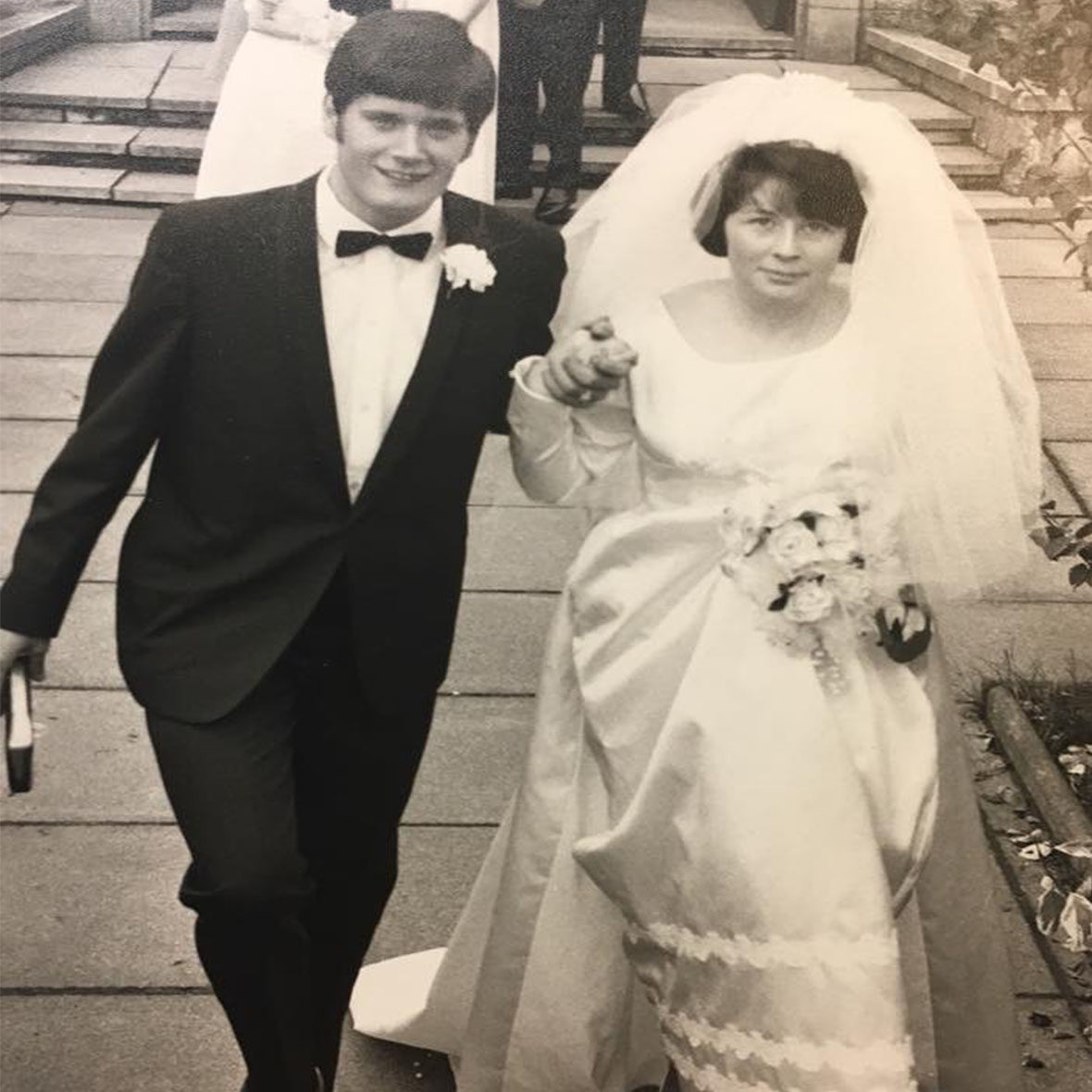 Black and white image of man in tuxedo and woman in wedding dress holding hands.