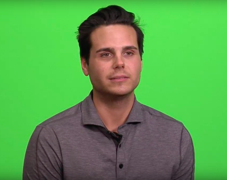 Man sitting in front of green screen.