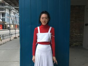 Woman with glasses, red turtleneck, white crop top and skirt standing in front of blue post.