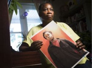 Woman holding photograph of her missing son.