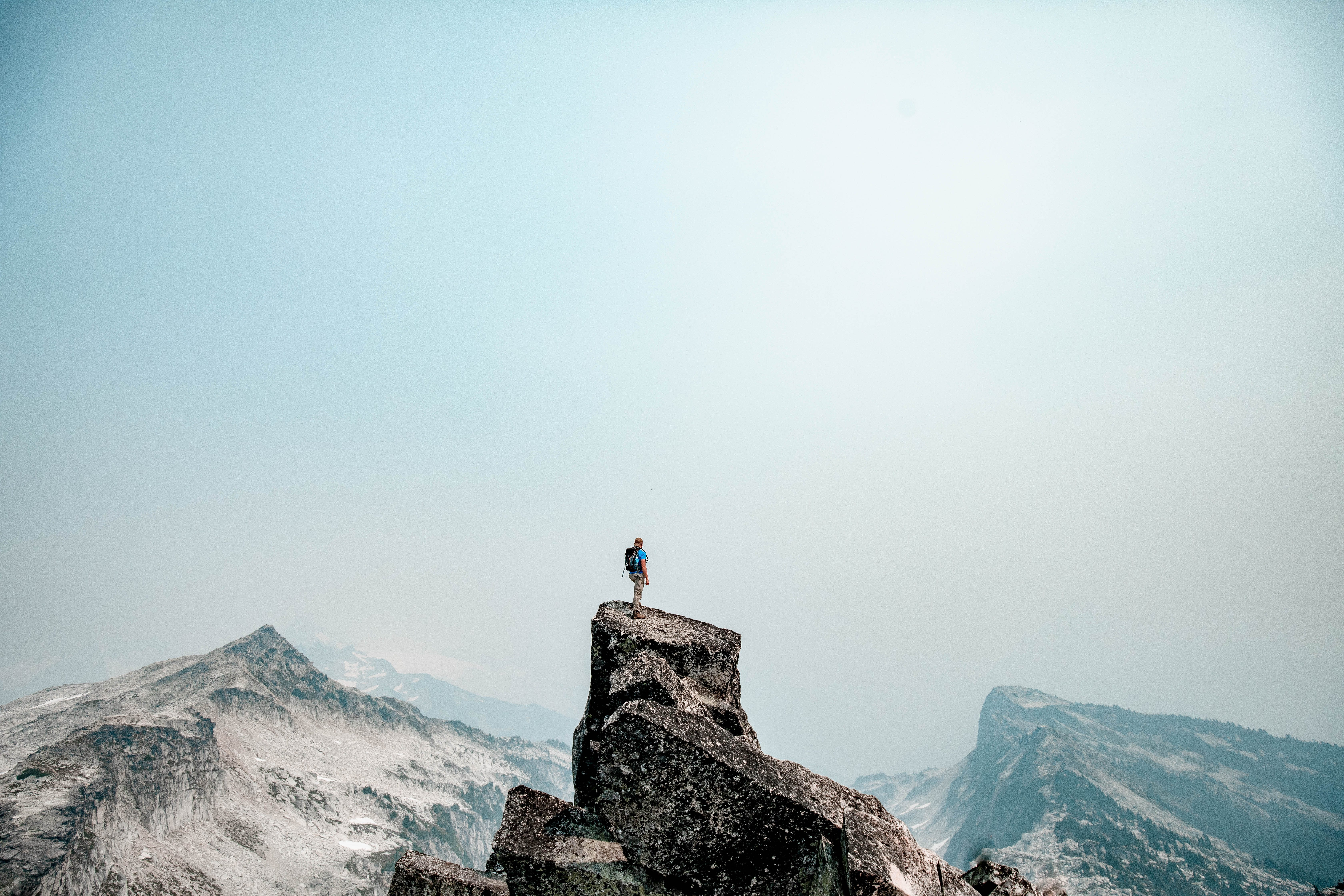 Man standing on cliff overlooking mountains.
