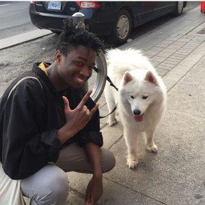 "Man squatting doing ""hang loose"" sign next to white dog."