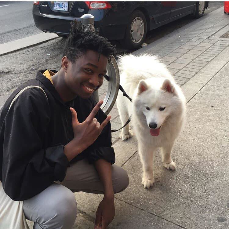 "Man squatting doing ""hang loose"" sign next to white dog."